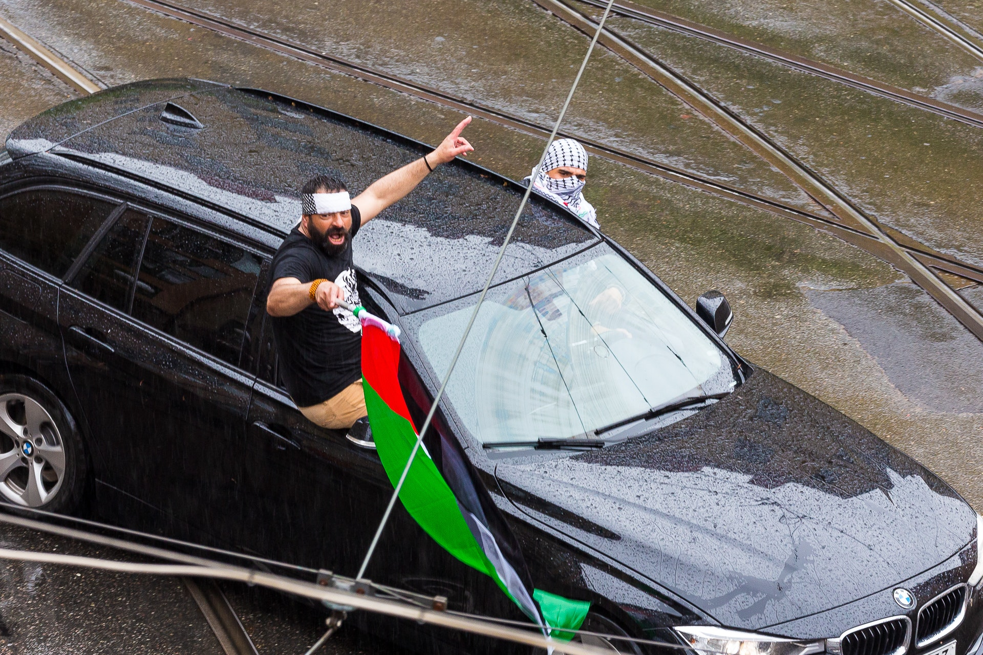 Palestinian protestors lean out of their cars