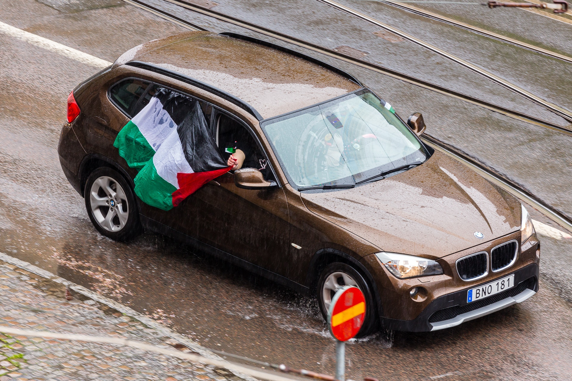 Soaked by the rain, the Palestinian flag flys flat on the car
