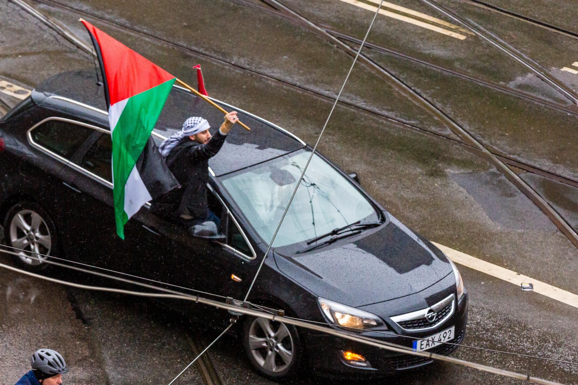 Protestor rides the windowsill as the car follows the convoy