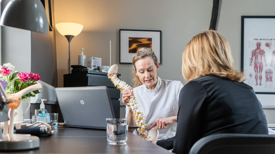 General Commercial Photography - Amy Beeton Osteopath explains the mechanics of the spine to her client.