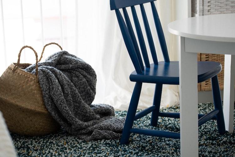 Apartamento Centro de Lisboa - Design de Interiores - home staging de decoração de quarto de bébé com manta grande e cesto em área de brincadeira, com cadeira de criança azul e mesa branca