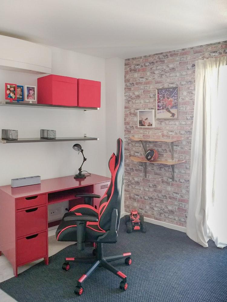 Apartamento Centro de Lisboa - Design de Interiores - Decoração de quarto de pré-adolescente com prateleiras feitas a partir de pranchas de skate, com secretária de metal vermelha e candeeiro preto ao estilo industrial, com papel de parede ed tijolo vermelho para reforçar o estilo industrial e cadeira gaming vermelha.