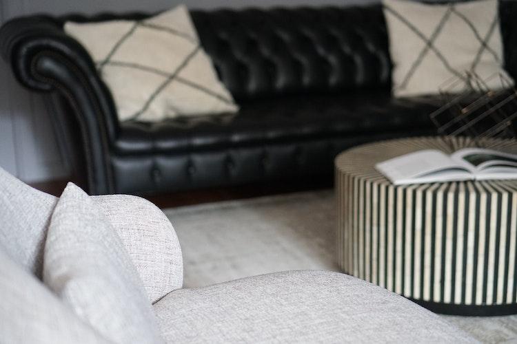 Apartamento Centro de Lisboa - Design de Interiores - Design e decoração de sala de jantar e sala de estar com sofá de estilo clássico Chesterfield em preto com mesa de centro redonda original e elegante