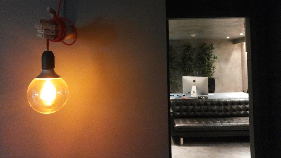 Stopline Films - Remodelação e Design de Interiores Escritório - Iluminação decorativa e Decoração de Zona de passagem com iluminação de uma mão a segurar uma lâmpada, iluminação criativa feita por medida com sala de cimento ao fundo