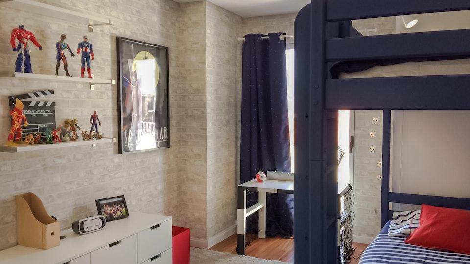 Apartamento Centro de Lisboa - Design de Interiores - Quarto de rapaz com tema de super heróis, com beliche azul escuro, móvel de arrumação IKEA, secretária transformada numa baliza para incentivar ao estudo e prateleiras com os seus objectos favoritos, o homem aranha, o capitão América e o Cristiano Ronaldo. Uma parte do quadro tem um papel de parede de tijolo branco com um cortinado de estrelas que brilham no escuro. Os têxteis são azul e branco às riscas, com apontamentos de vermelho.