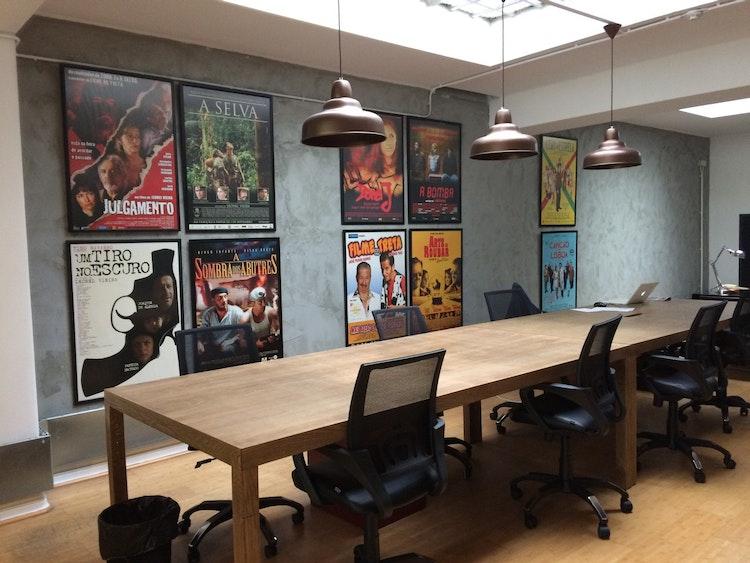 Stopline Films - Remodelação e Design de Interiores Escritório - remodelação, decoração e design de interiores - espaço de escritório com mesa única para trabalho de equipa com decoração de cartazes de filmes produzidos para motivar a equipa. Mesa feita por medida