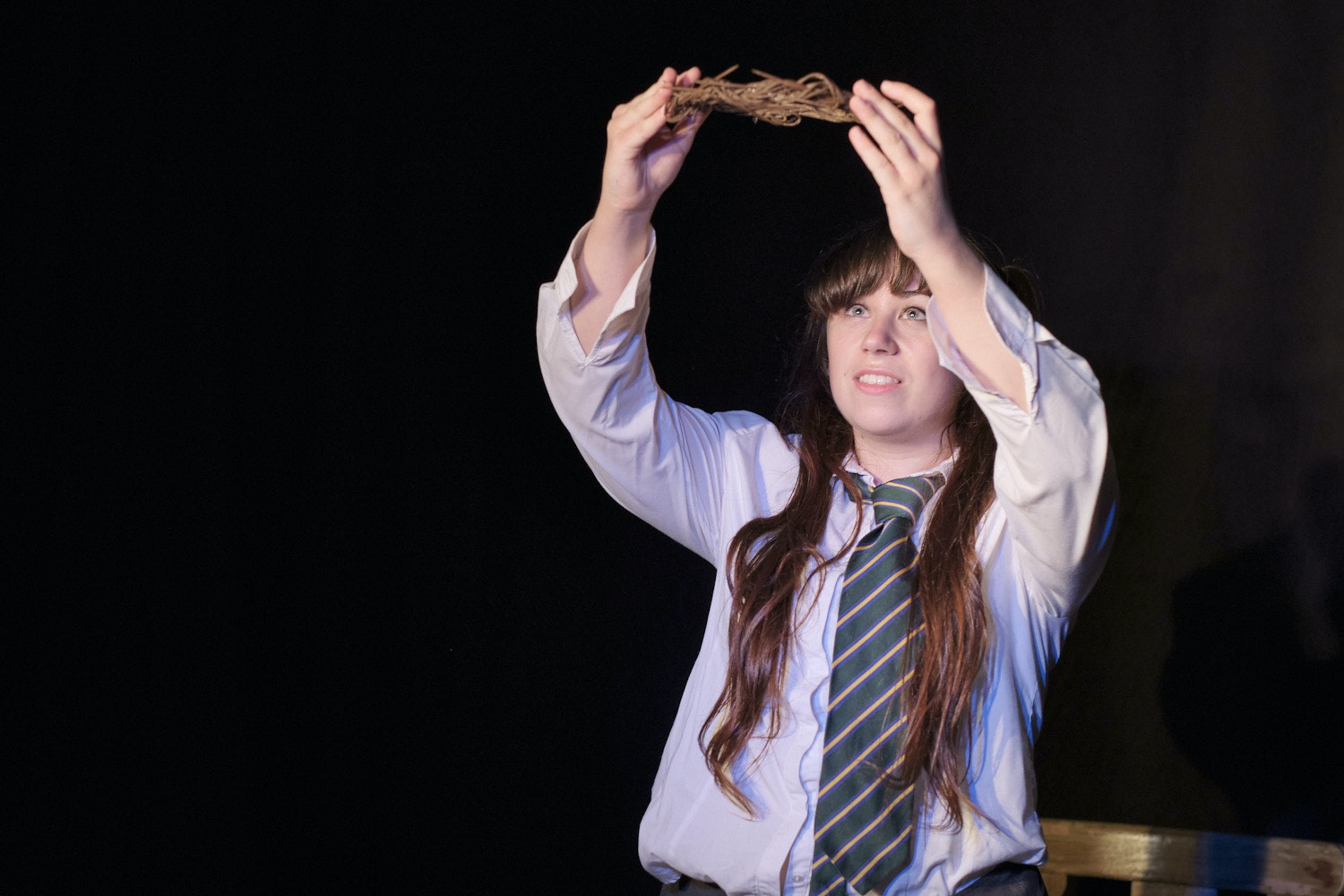 A girl in school uniform raises a crown of thorns. Image from 'The True Story Of The Little Girl Who Thought She Was The Second Coming Of Jesus Christ'