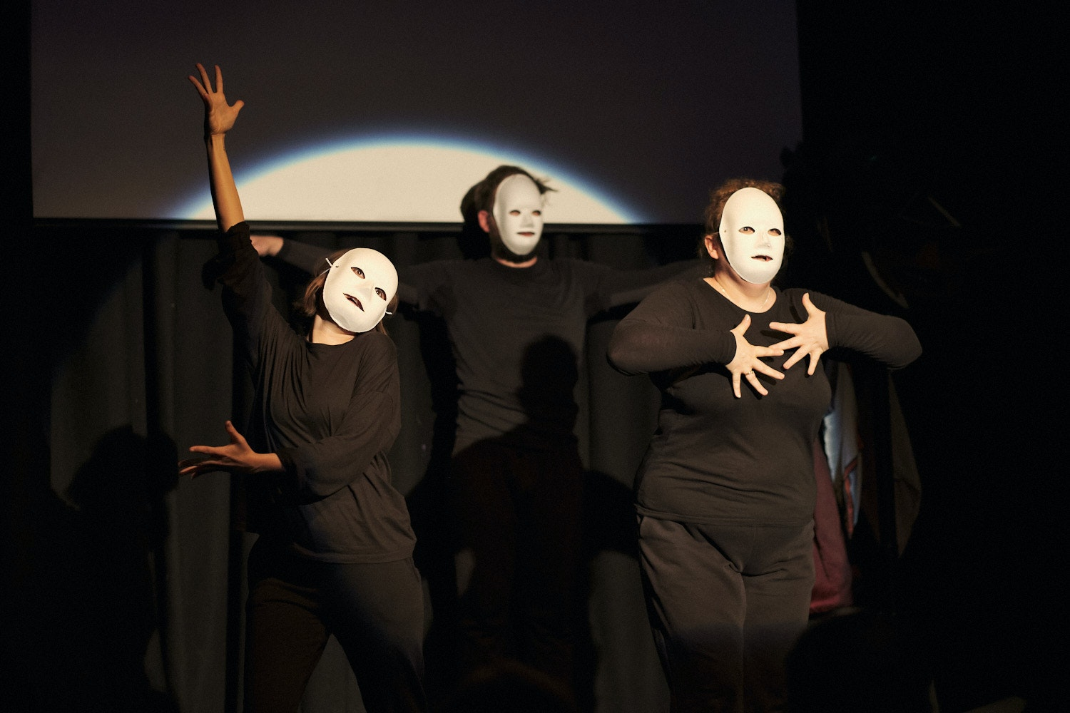 Three black-clad performers in blank white masks in 'Mayhem at the Cabaret Voltaire'