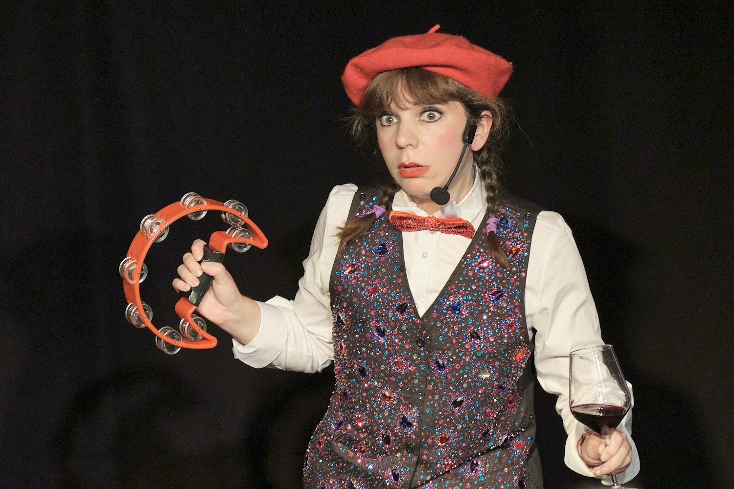 Anna Lou Larkin, with red beret and bow tie, tambourine and a glass of red wine, in 'Le Wine Club'