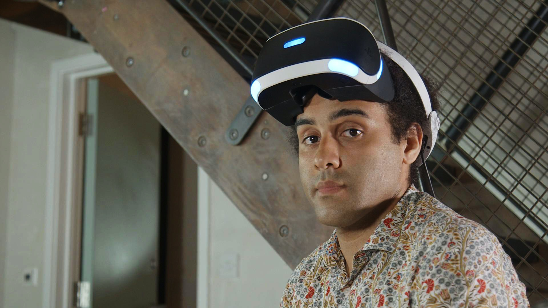 Actor Miles Mlambo galnces to camera between takes on Big Egg's Futurlab trailer shoot, wearing Sony Playstation VR headset